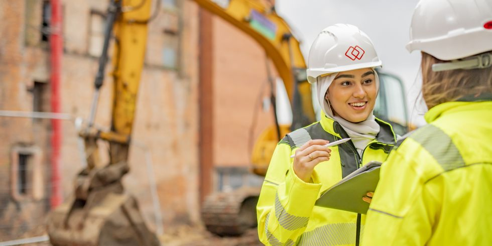 Husna Gul, Nottingham Trent University civil engineering apprentice, wearing a hard hat taking notes on a clipboard
